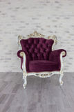 Antique chair from purple velvet in front of white room. Antique chair from purple velvet in front of white brick wall Stock Image