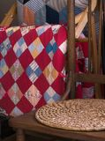 Antique Chair And Quilts. View of antique kitchen chair with rush pad, and antique quilts hanging on a rack Royalty Free Stock Photo
