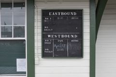Antique chalk board train schedule at Fort Langley heritage CN railway station. Heritage railway train schedule information chalk board for trains arriving and Stock Image