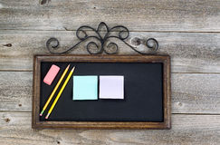 Antique chalkboard with supplies on rustic wood Stock Images