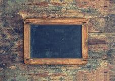 Antique chalkboard on wooden texture. Nostalgic background royalty free stock image