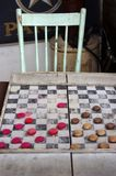 Antique checkers board game with chair in background. Vintage wooden red and brown checkers on old board game with old chair royalty free stock photos