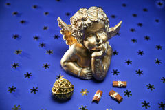 Antique cherub. In front of a blue background and some sticks of cinnamon. Illuminated with Dedo-lights Stock Photo