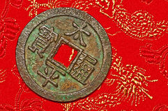 Antique chinese coin. On a red carpet Royalty Free Stock Photo