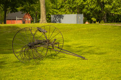 Antique Chisel Plow. Rusted brown, but intact, an antique chisel plow, used to break up and till the soil, sits on a lush green lawn near some trees with a red royalty free stock photos