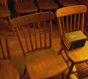 Antique church chairs with hymnals. Antique wooden chairs in 150 year old historic church royalty free stock photo