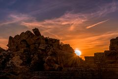 Antique city ruins under sunset with scattered clouds stock photos