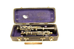 Antique clarinet musical instrument in old grunge case. Black antique clarinet musical instrument in old grunge case isolated on white Stock Photography