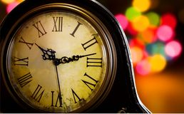 Antique clock. Old clock with christmas lights in the background stock image