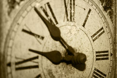 Antique clock. Antique, grungy clock close-up in sepia Royalty Free Stock Photo