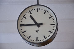 Antique clock with a circular dial. An old style clock with a circular dial suspended from a ceiling indicating that the time is 10:45 against a plain white Royalty Free Stock Images