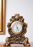 Antique clock in golden colors decorated with ornaments. And reliefs stock image