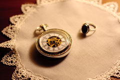 Antique clock and golden ring. A view of an old antique pocket watch and a golden ring on a fancy antique linen doily Royalty Free Stock Photos