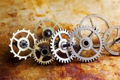Antique clock mechanism steampunk style cogs gears wheels macro view. Vintage rusty metal surface background, shallow. Depth of field Royalty Free Stock Images