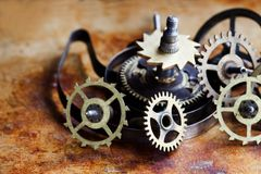 Antique clock mechanism steampunk style cogs gears wheels macro view. Vintage rusty metal surface background, shallow. Depth of field Stock Photography