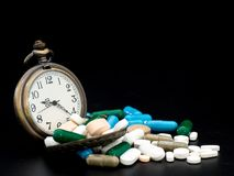 Antique clock on multicolored of drug and capsule is on the black background. Close up. We are against drugs anti drugs, cure in. Container for health.Heap of Stock Photo