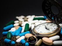 Antique clock on multicolored of drug and capsule is on the black background. Close up. We are against drugs anti drugs, cure in. Container for health.Heap of Royalty Free Stock Photography