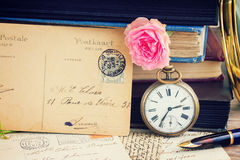 Antique clock on old books and letters background. Antique pocket clock with postcard on vintage books and letters background royalty free stock photography