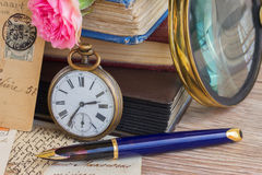 Antique clock on old books and letters background. Antique pocket clock on vintage books and letters background stock photo
