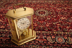 Antique clock on Persian rug. An antique clock with a bit of rust, styled like a gas lantern on a thick Persian rug Royalty Free Stock Photography