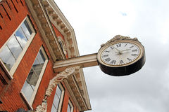 Antique clock. Photo of a large antique clock protruding from a building in a kent town Royalty Free Stock Photography