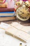 Antique  clock with pile of mail. Antique alarm clock with pile of mail and books Stock Photography