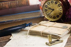 Antique  clock with pile of mail. Antique alarm clock with pile of books and mail Royalty Free Stock Images