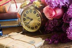 Antique  clock with pile of mail. Antique alarm clock with pile of mail and flowers Stock Photo