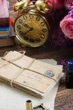 Antique  clock with pile of mail. Antique alarm clock with pile of vintage mail and flowers Royalty Free Stock Photos