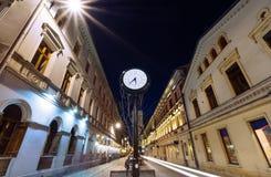 Antique clock on Piotrkowska Street, Lodz, in the evening. Royalty Free Stock Image