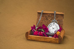 Antique clock with red petals. On brown background Royalty Free Stock Photos