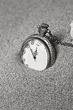 Antique clock in the sand. Black and white Stock Images