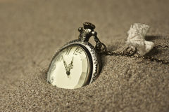 Antique clock in the sand. Gold colors Royalty Free Stock Photography