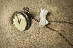 Antique clock in the sand. Golden colors Royalty Free Stock Photo