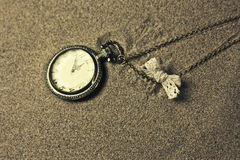 Antique clock in the sand. Golden colors Stock Photo