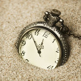 Antique clock in the sand. Macro Stock Photo