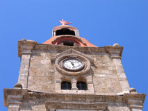 Antique clock on a stone tower. On the background of sky. Rhodes Stock Images