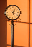 Antique Clock - vertical. An antique clock with map face on a warm orange background.  Vertical format Stock Images
