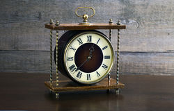 Antique clock. On a wooden table Stock Images