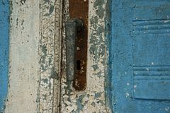 Antique closed door with metal door handle and vibrant white-blu paint royalty free stock photos