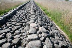 Antique cobblestone road. Through the field Stock Photos