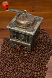 Antique coffee grinder. Old coffee grinder with coffee beans for context Stock Photo