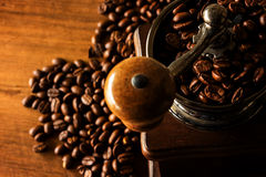 Antique coffee grinder with coffee beans. In the blurred background Stock Photography