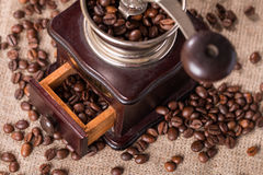 Antique coffee grinder and coffee beans. On burlap background Royalty Free Stock Photography
