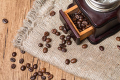 Antique coffee grinder and coffee beans. On burlap background Stock Images
