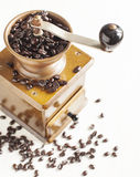 Antique coffee grinder with coffee beans. On white wooden background Royalty Free Stock Image