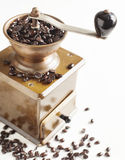 Antique coffee grinder with coffee beans. On white wooden background Royalty Free Stock Photography