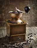 Antique coffee grinder with coffee beans. On wooden background Stock Photo