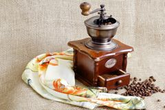 Old antique rare European coffee grinder, roasted fragrant coffee beans and scarf on jute rough background. Antique coffee grinder with grains of roasted coffee stock image