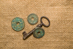Antique  coins  and keys  on old cloth Royalty Free Stock Photos
